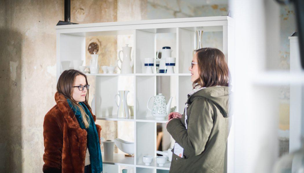 2 Besucherinnen vor einem Regal mit Exponaten aus Porzellan